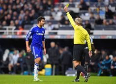 Diego Costa of Chelsea reacts as he is shown a yellow card by referee Martin Atkinson during the Barclays Premier League match between Newcastle United and Chelsea at St James' Park on December 6, 2014 in Newcastle upon Tyne, England.