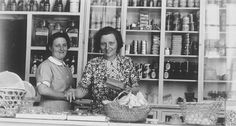 Two German Jewish refugee women stand behind the counter of the Elite Provision Store (delicatessen) in Shanghai. Pictured on the left is the owner, Gerda Harpuder; on the right is her cousin Kate Benjamin. In 1939 Hans and Gerda Harpuder sold their crystal, silver, and other family possessions shipped from Berlin in order to open a grocery store in Hongkew at 737 East Broadway.