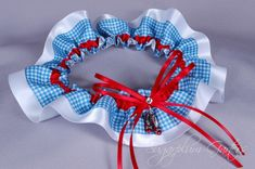 A Wizard of Oz wedding garter belt in red satin and blue gingham overlaying white satin, embellished with a Swarovski crystal, delicate red satin ribbons, and a ruby slipper charm. *** Including your event date with your order helps to ensure that your garter(s) will reach you in time for your event. *** WHEN WILL I RECEIVE MY ORDER? My garters are made-to-order and my current production time is 2-3 weeks. Shipping takes an additional 2-5 days for domestic orders, and 5-10 business days f...
