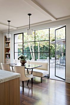 Beautiful space.  Huge window view from dining area - like the banquette seating on one side. Clean and simple. Floral arrangement and built-in bookcase soften the look.