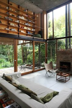 Spacious living room with abundant line from the large windows and a mezzanine library in this home located in Buenos Aires.