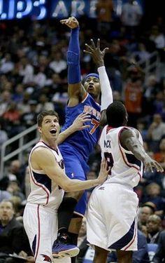 New York Knicks Carmelo Anthony, center, puts up a shot past Atlanta Hawks Kyle Korver, left, and Shelvin Mack