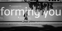 black and white street photography of a guy passing by.