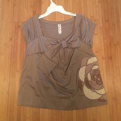 Anthropologie too Bow and flower detail cap sleeve top. Small stain noted in picture 2 otherwise in EUC Anthropologie Tops Blouses