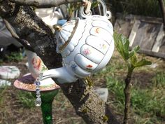 yard art - a tiny teapot with crystal coming out of the spout, hangs on a tree branch, reflects the sun so pretty