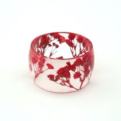 This wide resin ring features pressed red babys breath that is encased in resin. It is a wide band with clean lines, contemporary design and a subtle botanical pattern to complement any look. SIZE: This ring is available in a size 6, 8, 10, 12 and 14. This ring tends to run small
