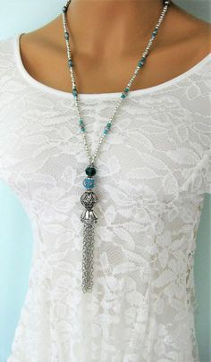Tassel Necklace handmade by Ralston Originals. This blue tassel necklace is made with a very unique blue bead, with crystals, and silver accents. The necklace is also made with a large sparkling blue crystal bead, and a large silver metal bead. The tassel is made with silver metal