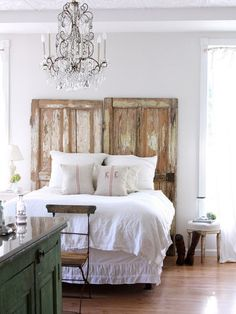 Chandelier and love the airy light feel of this room. Distressed furniture is nice, plus I like the green dresser topped with glass.