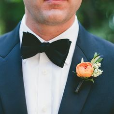 The groom's boutonniere will be an orange ranunculus, pink astilbe and green bay laurel wrapped in navy ribbon with the stems showing.