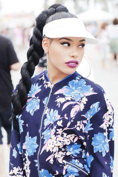 girl : ponytail : printed track jacket : visor : hoop earrings : blue