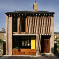 A mews house with protruding brickwork added to an existing Victorian home in Dublin, Ireland.
