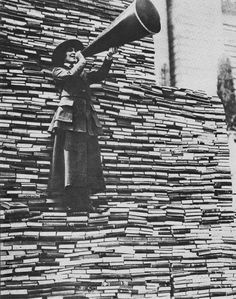 A woman standing atop of mountain of donated books outside the New York Public Library. During WWI, enemy countries used censors to create reading restrictions within their boundaries.  Concerned for our troops abroad, millions of people donated books to create a library of free books be sent to our troops while they were serving us overseas.