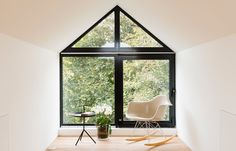 A dormer window with a thick black frame offers views of the garden from this reading room, which is one of three new loft spaces created for a home in south-east London by A Small Studio.