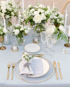 A Chic, Family-Oriented Destination Wedding in France | Martha Stewart Weddings - The delicate place settings included glass chargers, matte gold cutlery, tulip-shaped glasses, and porcelain plates beside low white centerpieces. Gold rims added an extra touch to glassware and place cards were tied around linen napkins. #weddingideas #weddingflowers