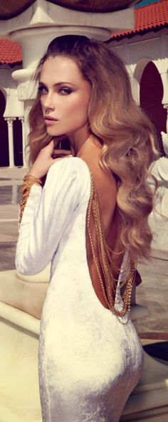 Gorgeous! Her hair, the gold chains hanging from a shimmery white dress, and a low back line!