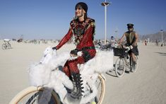 Bibi rides her bike on the Playa during the Burning Man 2015 'Carnival of Mirrors' arts and music festival in the Black Rock Desert of Nevada. Approximately 70,000 people from all over the world are gathering at the sold-out festival to spend a week in the remote desert to experience art, music and the unique community that develops.