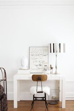 white home office and desk with silver touches into the lamp and wood chair. Love the baskets and buddha head !