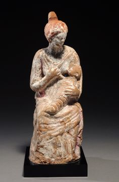 Hellenistic terracotta seated woman holding an infant, her hair combed into a melon coiffure pulled into a bun at back; traces of pigments. 4th-3rd century BC