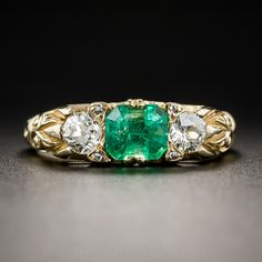Consummate Victorian artistry is exemplified in this classic emerald and diamond three-stone 'carved' ring adorned with elaborate scrolls and curvilinear engraving. This beautiful late-nineteenth/early-twentieth century jewel features a vibrant green emerald (it faces up much nicer than our highly magnified photo suggests), weighing 1.00 carat, set horizontally and accented left and right with a matched pair of sparkling old mine-cut diamonds. Four teeny-tiny rose-cut diamonds gl...