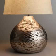 The round silhouette of our gorgeous Pewter Prema Punched Metal Table Lamp Base is full of texture and visual intrigue. The perfect size for an end table, buffet or nightstand, this affordable lamp base coordinates with our wide selection of table lamp shades, so you can create the perfect ensemble to fit your style, space and budget.