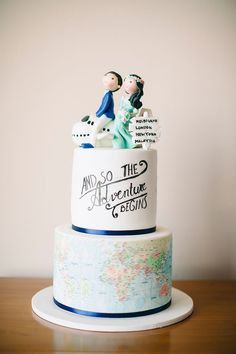 A travel-themed two-tiered wedding cake with world map, a thoughtful quote an topped with a figurine of the groom and bride