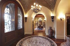 Another beautiful groin vault ceiling in a foyer with rounded arches accenting the shape and rounded double doors with whimsical iron scroll work.