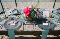"On the tabletops we used gray stone plates and pink florals to bring spring and earthy together. Each place setting has a favor for the guests: a terrarium that has a tag that reads ""keep love alive"""