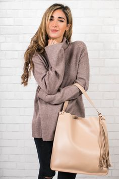 The Darling Detail Fashion Blogger is wearing a Hinge turtleneck, Frame jeans, and is holding a Sole Society Faux Leather Bucket Bag.