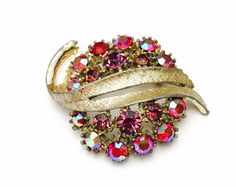 A personal favorite from my Etsy shop https://www.etsy.com/listing/492848613/vintage-art-brooch-gold-tone-red