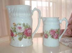 2 old water pitchers with roses