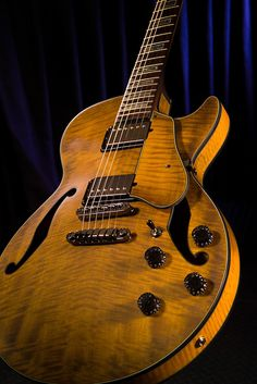 Beautiful woodgrained  electric Ibanez guitar standing on its edge with a dark blue curtain background.