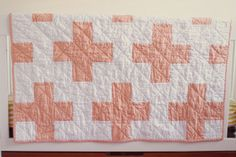 """this beautiful, modern quilt has peach plus signs stretching across the quilt top, is backed by a navy print, and quilted with diagonal lines stretching from edge to edge. natural cotton batting is sandwiched in between high quality fabric. the finished quilt measures 36""""x44"""" and is hand bound for a perfectly clean edge. the size is perfect for snuggling your babe and is big enough to grow with your toddler.  Please allow 3-4 weeks for production.Wash on gentle cyc..."""