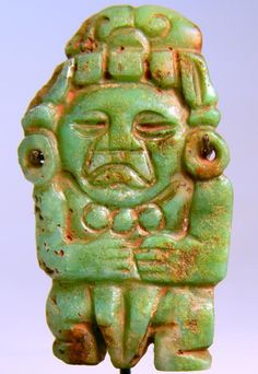 'Maya Jade Pendant'. A Pre-Columbian Mayan jade pendant in the form of a figure with an elaborate headdress and necklace of three circles, the surface rubbed with cinnabar. Central America. Ca. 500-800 AD. Height: 2 1/2 in. (6.5 cm). Intact. -Hixenbaugh Ancient Art LTD, New York- Mayan History, Earth Goddess, Mesoamerican, Native Indian, Mexican Folk Art, Global Art, Jade Pendant, Rocks And Minerals, Ancient Art