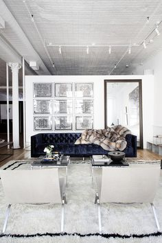Modern Living Room - A gallery wall of framed artwork behind a tufted couch in an industrial-style loft