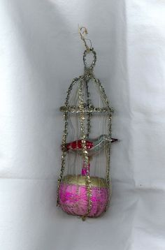 1900s vintage German wire wrapped Christmas ornament bird cage.6 & 1/2 inches tall by 2 inches wide. It is made up of an unsilvered pink and gold ball glass base on which a silvered bird is attached. The cage is made up of large silver crinkle wire and very fine silver spring wire. Victorian Christmas Ornaments, Retro Christmas, Glass Christmas Ornaments, Pink Christmas, Christmas Wrapping, All Things Christmas, Christmas Trees, Feather Tree, Bird Cage