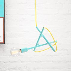 Designer pendant light in white brick kitchen. Here in colorful and surprising combination of turquoise patina and yellow braided cord. Unique lighting for urban loft apartment or mid-century modern interior.