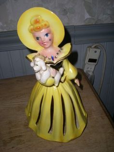 This auction is for a vintage Napkin lady in Yellow holding a Poodle. She was made by Kreiss. She has a sticker on the bottom that reads Japan and has Kreiss & Company stamped on the bottom. She has all of her rhinestones and is in very nice condition. The only flaw I could find is there is a stress crack on one of the pleats of her skirt. It doesn't go all the way thru. Other then that she just needs a wash. These are getting harder to find. A great addition to anyone's collectio...