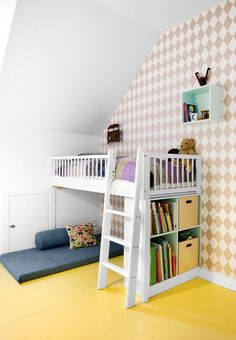 Children's room with books, toys and a cozy corner under the bed. We love the graphic wallpaper and yellow floors.