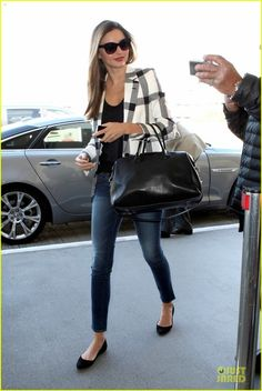 Miranda Kerr in black-and-white Stella McCartney blazer, Frame Denim skinny jeans, and black t-shirt paired with black Givenchy flats, Oliver Peoples sunglasses, and Givency bag.