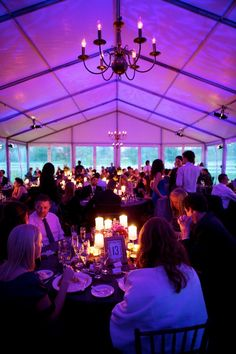 A purple glow and candle light ambiance as guests dine before enjoying an evening of fun and frivolity. Jen Kroll Photography. A Day in May Events. Special Events Rental.