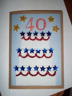 cake made of white felt w/ red glitter piping & blue stars w/ '40' on the top & gold stars around.