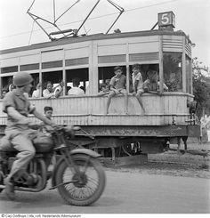 Cas Oorthuys/ Kinderen hangen achter uit een rijdende elektrische tram te Jakarta, Indonesië (1947)