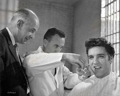 Director Richard Thorpe, looks on as Elvis get his 'haircut'.(Elvis had two wigs,an Intermediate haircut and a Butch haircut)MGM stage 23,Scene 11,Interior Prison Barber shop. 20th May 1957. Scene 11A take 2 can be seen in 'Elvis In Hollwood'.