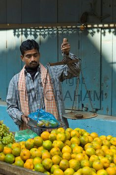 Weighing oranges the old fashioned way, Varanasi, Benares, India