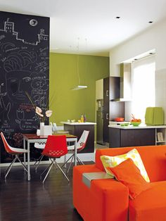 Tres zonas en una  Aquí el salón comparte espacio con la cocina y con un mini comedor en medio de ambos. Se diferencian con un pequeño tabique pintado de pizarra, un armario bajo y distintos suelos. Ideal para apartamentos.