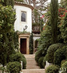 House in Malibu, CA.  The front door is framed by a French 18th-century stone surround and lush greenery.