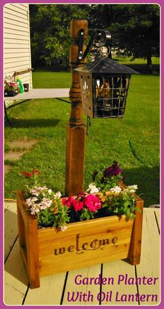 Garden Planter  ~ Olde Rustic Bed Post standing in a wooden garden planter box, with an Olde Metal oil lantern hanging from the bed post. Created By K Avery