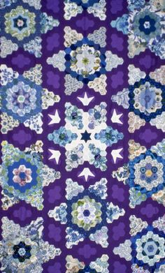 Hexagon Mosaic patchwork top pieced to form a snowflake design, made from purple, blue and whit cotton fabrics. It was made by Helen Otway-Ruthven for her son.