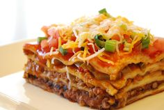 HOW TO MAKE MEXICAN LASAGNA RECIPE   Mexican Lasagna. Lasagna noodles are heated with a hearty mix of hamburger, refried beans, oregano, cumin and garlic, with salsa spooned over. Finished with sharp cream, green onions, olives and Pepper Jack cheddar, the goulash gets one more concise preparing to liquefy the cheddar.
