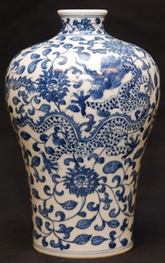 CHINESE QIANLONG PORCELAIN DRAGONS VASE Chinese Qing Dynasty Qianlong hand painted blue and white porcelain mei ping vase having dragon and lotus blossom design throughout. Holds Qianlong (1736-1795) six character archaic reign mark to bottom. Measures 8 5/8 height x 6 1/2 width (21.9cm x 16.5cm).